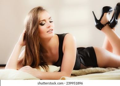 Full length sensual woman in black lingerie with long hair lying on carpet in retro vintage high heels shoes