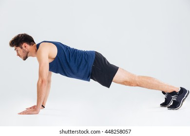 Full length of serious young man athlete doing push ups over white background