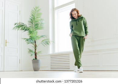 Full length shot of active pleased young woman with slim body, keeps hands in pockets of tracksuit, focused down, ready for doing cardio exercises, has determined look, pilates exercising indoor
