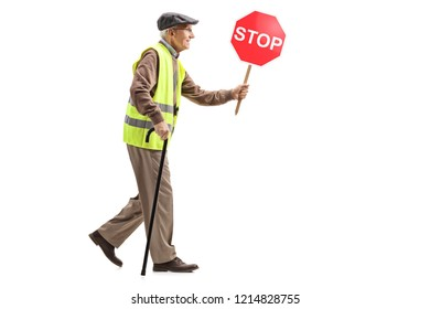 Full length shot of asenior man walking with a cane, wearing safety vest and holding a stop sign isolated on white background