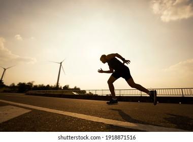Vollständiger Schuss des Athleten Läufer auf der Straße laufen. Männlicher Läufer, der im Freien sprintet. schwarzer Schatten.