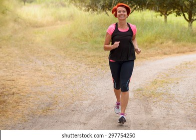 Full Length Shot of an Athletic Middle Aged Redhead Woman Jogging Along the Pathway and Smiling at the Camera.