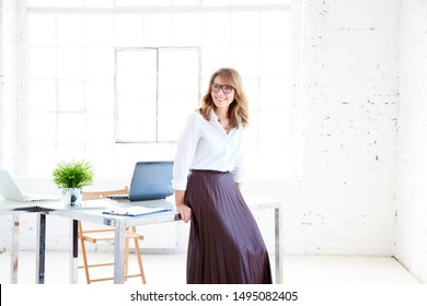 Full length shot of attractive middle aged businesswoman wearing glasses while standing at office desk and looking away.