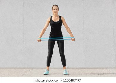 Full length shot of attractive sporty woman dressed in black sportsclothes, holds rubber resistance band, has workout at home, poses against grey background. People, endurance, determination