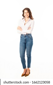 Full length shot of attractive young woman wearing white shirt and blue jeans while posing at isolated white background.