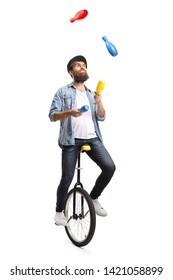 Full length shot of a bearded man on a unicycle juggling with clubs isolated on white background