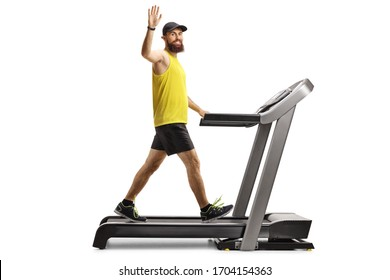 Full length shot of a bearded man in sportswear walking on a treadmill and waving isolated on white background