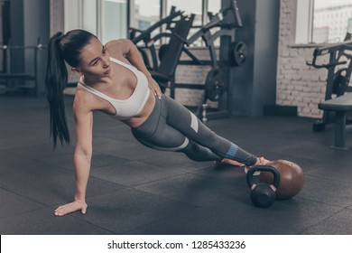 Full length shot of a beautiful dark haired athletic woman exercising at the gym, doing side plank, copy space. Young sportswoman with fit and toned body working out. Health, sports motivation concept