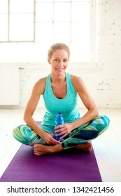 Full length shot of beautiful mature woman relaxing after yoga workout and holding a bottle of water in her hand.