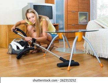 Full length shot of blonde woman cleaning with vacuum cleaner at home