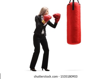 Full length shot of a businesswoman with red boxing gloves exercising with a punching bag isolated on white background