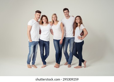 Full Length Shot of Closed Young Friends Smiling at the Camera in Plain White Shirts with Copy Space and Blue Jeans, Captured in Studio on White Background.