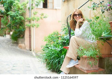 Full length shot of confident smiling woman sitting on stairs with green plants on the street and text messaging.
