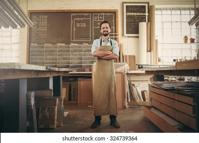 Full length shot of a craftsman standing confidently with his arms folded in the middle of his workshop studio smiling confidently at the camera