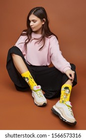 "Full length shot of a dark-haired girl, sitting on a floor. She wearing pink sweatshirt, black culottes, yellow artwork socks with ""Kiss"" by Klimt painting and white sneakers."