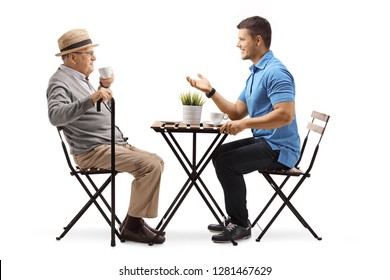 Full length shot of an elderly man and young man sitting at a table having a conversation and drinking coffee isolated on white background