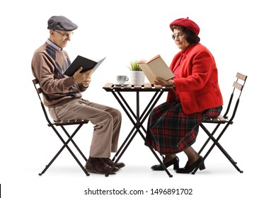 Full length shot of an elderly man and woman at a cafe reading books isolated on white background
