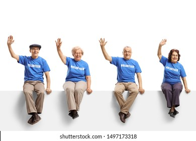 Full length shot of a elderly volunteers sitting on panel and waving isolated on white background