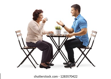 Full length shot of an elderly woman and a young man chatting and drinking coffee isolated on white background