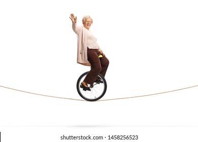 Full length shot of an elderly woman riding a unicycle on a rope and looking at the camera isolated on white background