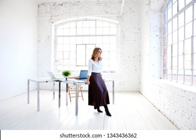 Full length shot of elegant middle aged businesswoman standing at office desk and looking out the window while deep in thought.