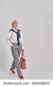 Full length shot of elegant middle aged caucasian woman wearing business attire and glasses looking away while posing with handbag isolated over grey background. Vertical shot