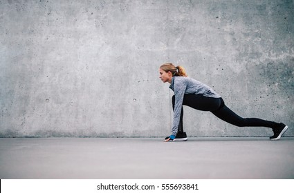 Full length shot of fit young woman doing stretching workout. Fitness model exercising in morning outdoors.
