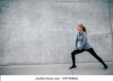Full length shot of fit young woman doing stretching workout in morning. Fitness model exercising outdoors.