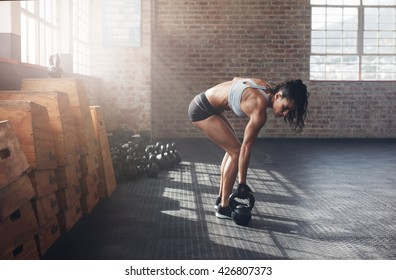 Full length shot of fitness woman doing exercising with kettle bell. Determined female model about to start her fitness regime at the  gym.
