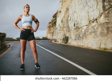 Full length shot of fitness woman standing with her hands on hips and looking away. Female athlete taking a break from running on highway around the mountains.