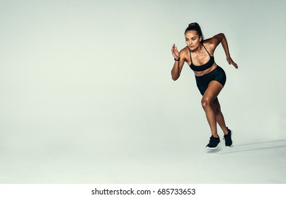 Full length shot of fitness woman running over grey background. Hispanic female runner working out in studio.