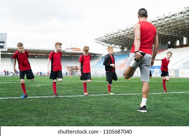 Full length shot of  football coach showing stretching exercises to group of boys during warm up before practice in outdoor stadium