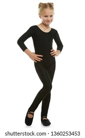 Full length shot of girl with ballet buns, wearing black leotard, glossy leggins and gym shoes. The child with slight smile is posing with hands on hips looking at camera against white background.