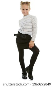 Full length shot of girl with ballet buns, wearing blouse with ruffles, black skirt with belt and black tights. The girl is touching her leg, looking at the camera, posing against snowy background.