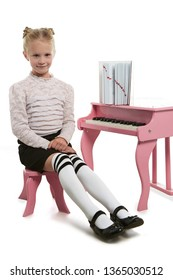 Full length shot of girl with ballet buns, wearing blouse with ruffles, black skirt and striped kneesocks. The child is looking at camera, sitting straight on small chair near piano with book on it.