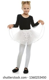 Full length shot of girl with hair buns, wearing glossy leggins, and bouffant chiffon skirt. The child with slight smile is posing raising skirt to sides up, looking at camera on white background.