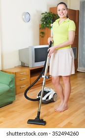 Full length shot of girl in skirt cleaning with vacuum cleaner at home