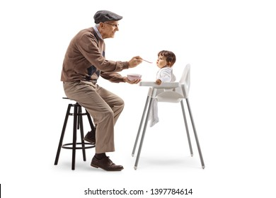 Full length shot of a grandfather feeding a baby with a spoon isolated on white background