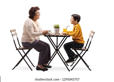 Full length shot of a grandmother sitting at a coffee table and talking to her grandson isolated on white background