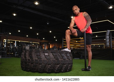 Full length shot of a handsome African athletic man looking to the camera fiercely, resting after sledgehammer crossfit workout. Powerful sportsman resting after hitting huge tire with sledgehammer