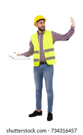 Full length shot of handsome beard young engineer explaining something and holding a clipboard, guy wearing caro shirt and jeans with a yellow vest and yellow helmet, isolated on white background