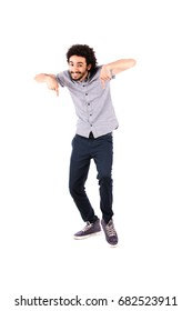 Full length shot of handsome happy young man smiling and pointing down, guy wearing gray t-shirt and jeans, isolated on white background