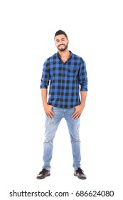 Full length shot of handsome happy beard young man smiling and standing confidently, guy wearing blue caro shirt and jeans, isolated on white background