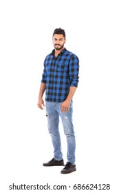 Full length shot of handsome happy beard young man smiling and wearing blue caro shirt and jeans, isolated on white background