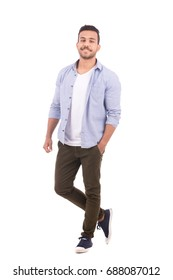 Full length shot of handsome happy beard young man smiling and standing confidently, guy wearing gray shirt and brown trousers, isolated on white background