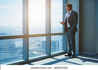 Full length shot of a handsome mature business executive in a corporate suit, standing next to large windows in a top floor office, typing a text message on his phone
