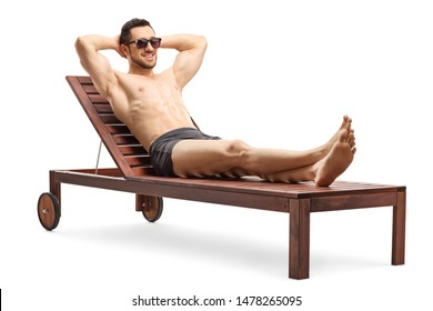 Full length shot of a handsome young man sunbathing on a lounge chair isolated on white background