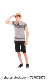 Full length shot of handsome young man wearing gray t-shirt and black short with a beige hat, guy looking away, isolated on white background