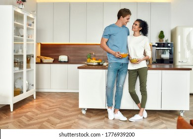 Full length shot of happy couple, vegetarians looking at each other while standing in the kitchen. Young man and woman holding smoothie bowls. Vegetarianism, healthy food, diet, stay home concept