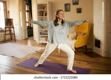 Full length shot of happy energetic mature woman in casual clothes exercising at home because of social distancing, practicing yoga on mat, standing in warrior ii pose. Age, wellness and health - Shutterstock ID 1715225080